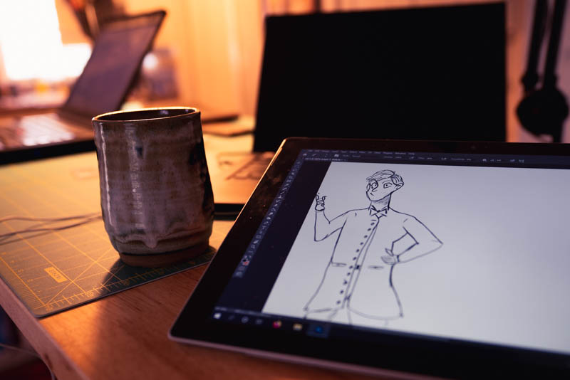 At the worktable with a sketch of one brother in gentlemanly coats with a coffee mug and laptop to the side.