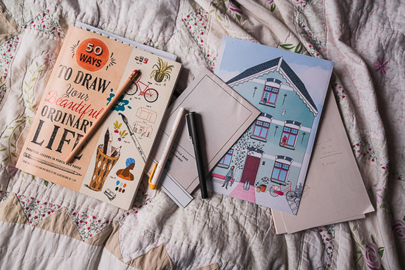 50 Ways to Draw Your Beautiful Ordinary Life drawing textbook with a few scattered pencils