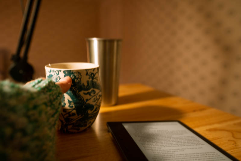 My e-reader with coffee in hand as the sun's rays pour in.