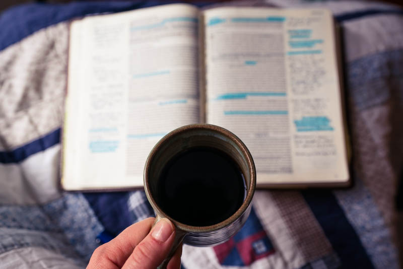 Open book with coffee in hand as the morning sun pours in.