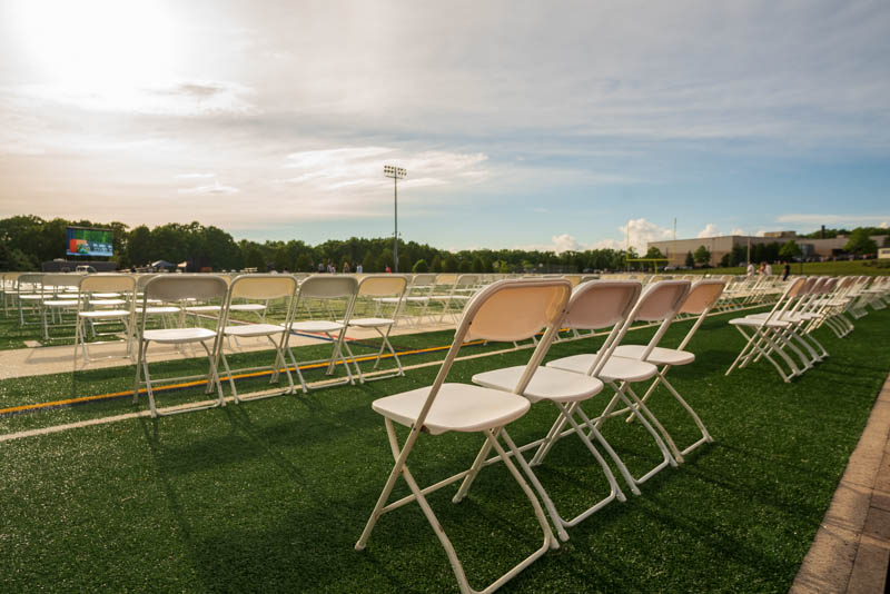 And empty football field filled with chairs ready to welcome the high school graduating class of 2021
