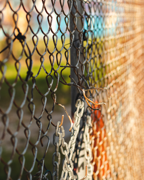 Chain link fence with a small hole in the center. Photo by Ussama Azam on Unsplash