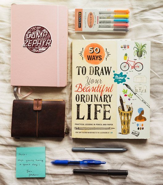 50 Ways to Draw Your Beautiful Life book, notebooks, and pens all lined up.