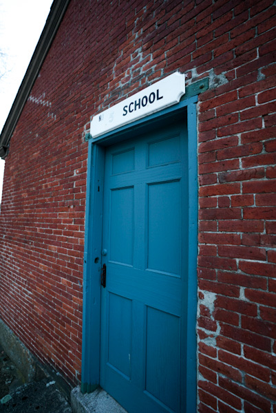 Historic New England schoolhouse with a blue door in the snow.