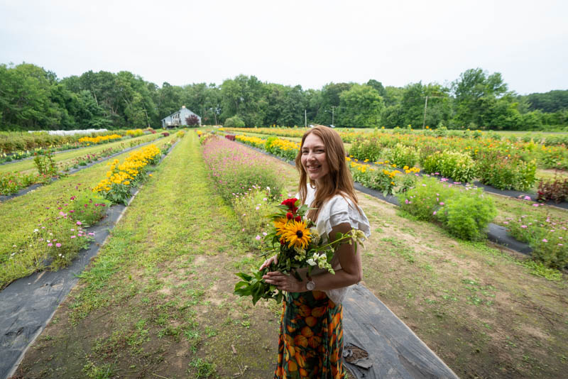 A picture of me standing with freshly cut summer flowers in hand at the Peterson Farms