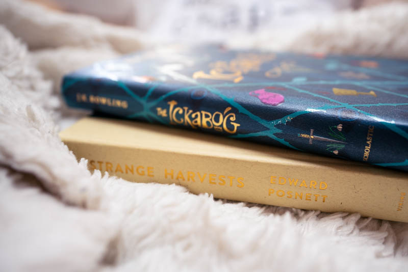 The Ickabog by JK Rowling sits on the bed on top of Bryan's current read, Strange Harvest by Edward Posnett.