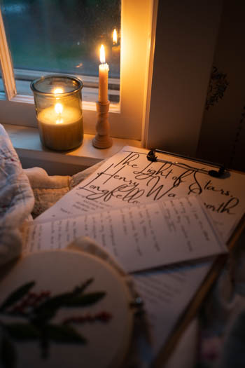 Reading the Light in Stars by candlelight near the windowsill on a stormy evening