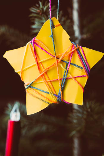 A beautiful yellow paper ornament, in the shape of a five pointed star, wrapped in some lovely multi-colored string to hang it on the tree.