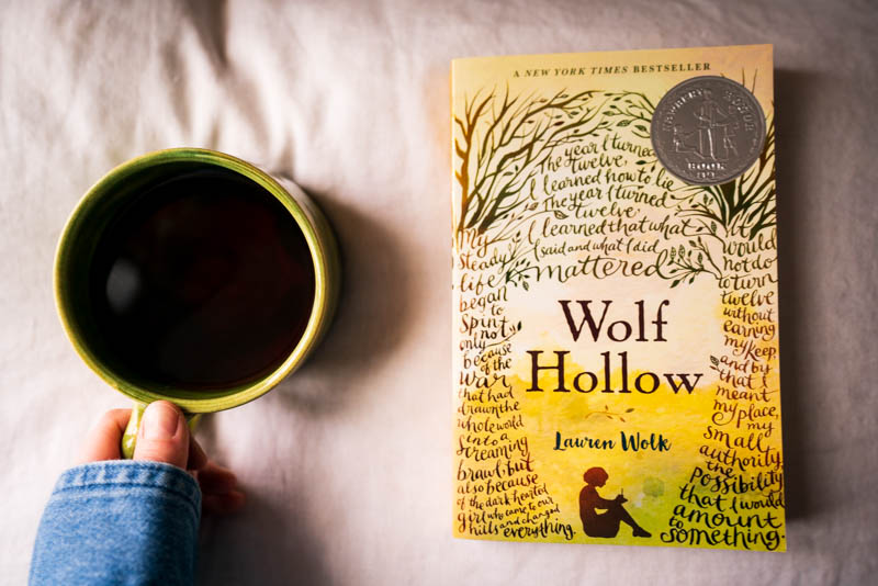 Wolf Hollow by Lauren Wolk paperback edition, with a cup of black coffee in a green ceramic mug crafted by a dear friend, Sarah.