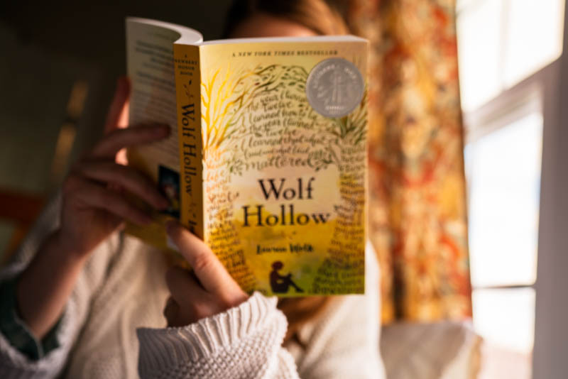 Reading the paperback print of Wolf Hollow by Lauren Wolk on a sunny afternoon.